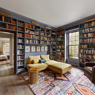 Cette photo montre une salle de séjour avec une bibliothèque ou un coin lecture éclectique avec un mur violet, un sol en bois brun et un sol marron.