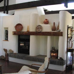 サンルイスオビスポの中サイズのサンタフェスタイルのおしゃれなファミリールーム (白い壁、濃色無垢フローリング、標準型暖炉、コンクリートの暖炉まわり、テレビなし) の写真