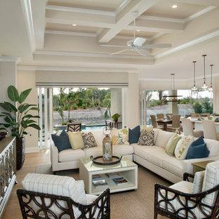 マイアミの中サイズのトロピカルスタイルのおしゃれなファミリールーム (ベージュの壁、淡色無垢フローリング、暖炉なし、壁掛け型テレビ、茶色い床) の写真