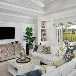マイアミの中サイズのトロピカルスタイルのおしゃれなファミリールーム (ベージュの壁、淡色無垢フローリング、暖炉なし、壁掛け型テレビ、ベージュの床) の写真