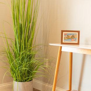 Imagen de sala de estar abierta, industrial, pequeña, con paredes grises, suelo vinílico y suelo marrón