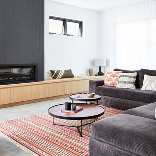 Contemporary family room in Sydney with white walls, ceramic floors, a standard fireplace, a wood fireplace surround and grey floor.