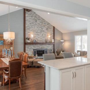 Foto de sala de estar abierta, tradicional renovada, extra grande, con paredes grises, suelo de madera oscura, estufa de leña, marco de chimenea de piedra y suelo marrón