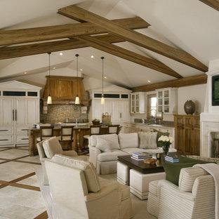 Immagine di un soggiorno chic aperto con pareti beige, camino classico, cornice del camino in pietra e TV a parete