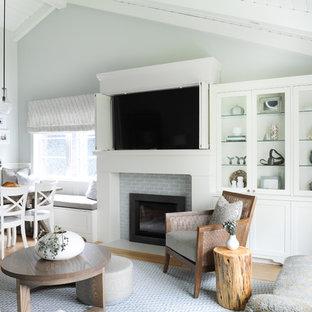 Idée de décoration pour une petite salle de séjour marine ouverte avec un mur gris, un sol en bois clair, une cheminée standard, un manteau de cheminée en carrelage, un téléviseur dissimulé et un sol marron.