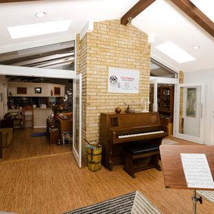 Foto de sala de estar con rincón musical abierta, tradicional renovada, de tamaño medio, con paredes grises y suelo de corcho
