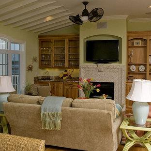 Eklektisches Wohnzimmer mit beiger Wandfarbe, braunem Holzboden, Kamin und freistehendem TV in Raleigh