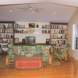 Aménagement d'une salle de séjour avec une bibliothèque ou un coin lecture exotique de taille moyenne et ouverte avec un mur blanc, un sol en bois clair, un téléviseur indépendant et un sol jaune.