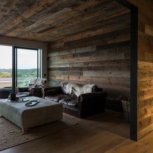 オークランドの中サイズのインダストリアルスタイルのおしゃれなファミリールーム (マルチカラーの壁、淡色無垢フローリング、標準型暖炉、茶色い床) の写真