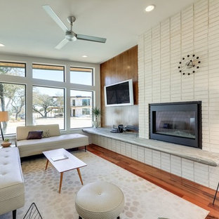 Family room - 1960s open concept medium tone wood floor and brown floor family room idea in Austin with white walls, a brick fireplace, a wall-mounted tv and a standard fireplace
