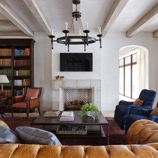 Foto de sala de estar con biblioteca cerrada, mediterránea, con paredes blancas, chimenea tradicional, marco de chimenea de baldosas y/o azulejos y televisor colgado en la pared