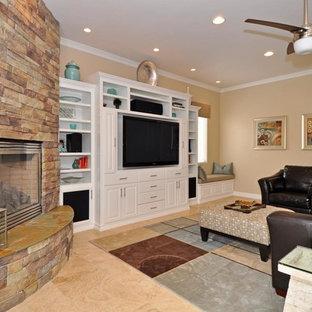 Immagine di un soggiorno design di medie dimensioni e chiuso con pareti beige, pavimento in travertino, camino sospeso, cornice del camino in pietra e parete attrezzata
