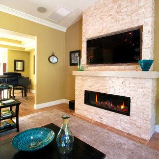 Imagen de sala de estar abierta, marinera, grande, con paredes amarillas, suelo de travertino, chimenea lineal, marco de chimenea de piedra y televisor colgado en la pared