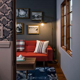 Imagen de sala de estar cerrada, marinera, pequeña, sin chimenea, con paredes grises, suelo de madera en tonos medios y televisor independiente