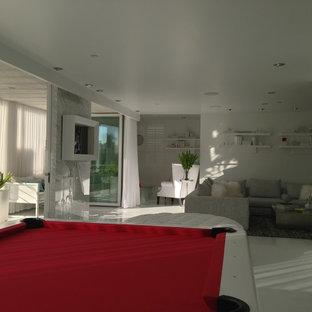 Offener, Großer Moderner Hobbyraum mit weißer Wandfarbe, Hängekamin, Kaminumrandung aus Stein, Porzellan-Bodenfliesen und weißem Boden in San Diego