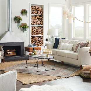 Mid-sized eclectic enclosed dark wood floor and brown floor family room photo in Charlotte with white walls, a wood stove, a plaster fireplace and no tv