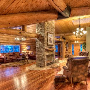 Ispirazione per un ampio soggiorno country stile loft con pareti beige, pavimento in legno massello medio, camino bifacciale, cornice del camino in pietra e nessuna TV