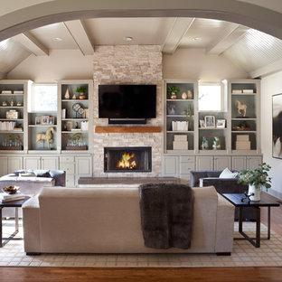 Foto di un soggiorno chic di medie dimensioni e chiuso con pareti beige, pavimento in legno massello medio, camino sospeso, cornice del camino in pietra, TV a parete e pavimento marrone