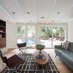 Foto de sala de estar vintage con paredes blancas, suelo de madera en tonos medios, chimenea de doble cara y televisor colgado en la pared