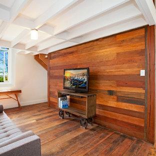 Inredning av ett industriellt allrum, med mellanmörkt trägolv, en fristående TV och bruna väggar