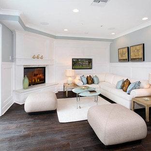 オレンジカウンティの小さいトラディショナルスタイルのおしゃれな独立型ファミリールーム (グレーの壁、濃色無垢フローリング、茶色い床、標準型暖炉、タイルの暖炉まわり) の写真
