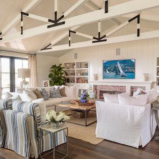Maritimes Wohnzimmer mit weißer Wandfarbe, Kamin, Kaminsims aus Backstein, Wand-TV, braunem Boden und braunem Holzboden in Orange County