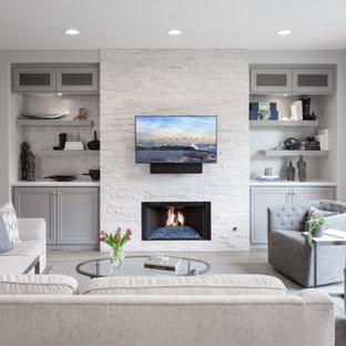 Offenes Klassisches Wohnzimmer mit grauer Wandfarbe, Kamin, Kaminumrandung aus gestapelten Steinen, Wand-TV und grauem Boden in Orange County