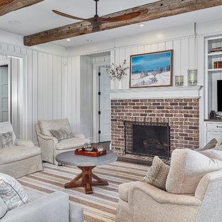 他の地域のビーチスタイルのおしゃれな独立型ファミリールーム (白い壁、無垢フローリング、標準型暖炉、レンガの暖炉まわり、埋込式メディアウォール) の写真
