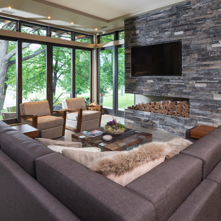 Family room - small modern open concept concrete floor family room idea in Minneapolis with beige walls, no fireplace, a stone fireplace and a wall-mounted tv