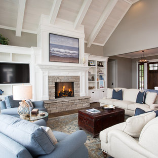 Medium sized nautical open plan family and games room in Other with beige walls, dark hardwood flooring, a standard fireplace, a stone fireplace surround, a wall mounted tv and brown floors.
