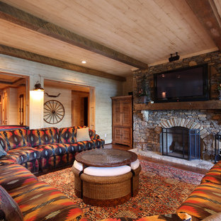 Family room - large rustic open concept medium tone wood floor and brown floor family room idea in Atlanta with a standard fireplace, a stone fireplace, a wall-mounted tv and beige walls