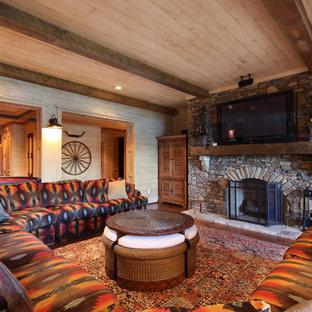 アトランタの広いラスティックスタイルのおしゃれなオープンリビング (標準型暖炉、石材の暖炉まわり、壁掛け型テレビ、ベージュの壁、無垢フローリング、茶色い床) の写真