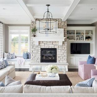 Imagen de sala de estar marinera con paredes grises, suelo de madera oscura, chimenea tradicional, marco de chimenea de piedra y pared multimedia