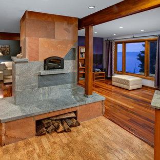 クリーブランドの巨大なコンテンポラリースタイルのおしゃれなオープンリビング (コルクフローリング、両方向型暖炉、石材の暖炉まわり、壁掛け型テレビ) の写真