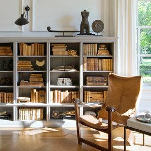 Modelo de sala de estar con biblioteca abierta, clásica renovada, de tamaño medio, sin chimenea y televisor, con paredes blancas y suelo de madera en tonos medios