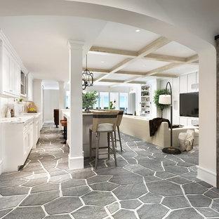 Immagine di un grande soggiorno minimal chiuso con pareti grigie, camino classico, cornice del camino in pietra, nessuna TV, pavimento grigio e angolo bar