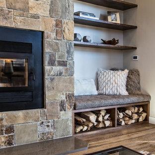 Idée de décoration pour une très grande salle de séjour tradition ouverte avec un mur beige, un sol en bois clair, une cheminée standard, un manteau de cheminée en pierre, aucun téléviseur et un sol marron.