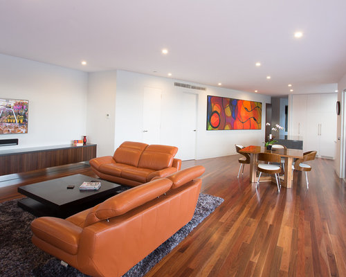 contemporary family room in melbourne with white walls dark hardwood floors and no fireplace