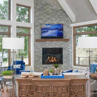 Diseño de sala de estar abierta, costera, con suelo de madera clara, chimenea de esquina, paredes grises y marco de chimenea de piedra