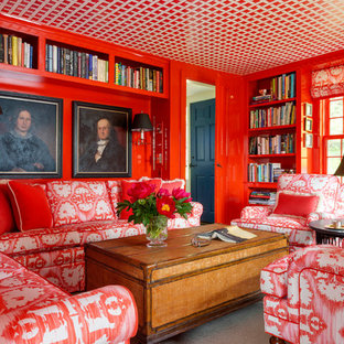 Cette image montre une petite salle de séjour avec une bibliothèque ou un coin lecture bohème fermée avec un mur rouge.