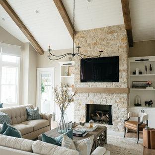 Cette image montre une grand salle de séjour rustique fermée avec un mur beige, un sol en bois clair, une cheminée standard, un manteau de cheminée en pierre, un téléviseur encastré et un sol marron.
