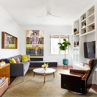 Idées déco pour une grande salle de séjour avec une bibliothèque ou un coin lecture éclectique fermée avec un mur blanc, un sol en bois brun, aucune cheminée, un téléviseur encastré et un sol marron.