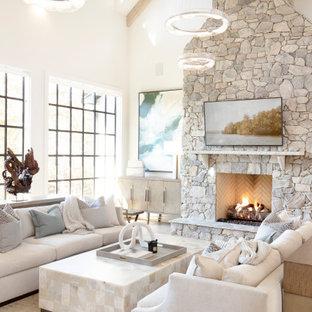 他の地域の広いビーチスタイルのおしゃれなオープンリビング (白い壁、淡色無垢フローリング、標準型暖炉、石材の暖炉まわり、壁掛け型テレビ、茶色い床、板張り天井) の写真