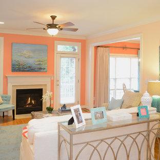 Exemple d'une salle de séjour éclectique de taille moyenne et fermée avec un mur orange, un sol en bois clair, une cheminée standard, un téléviseur indépendant et un manteau de cheminée en pierre.