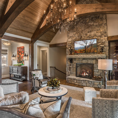 Family room - huge rustic open concept dark wood floor family room idea in Other with a standard fireplace, a stone fireplace, gray walls and a wall-mounted tv