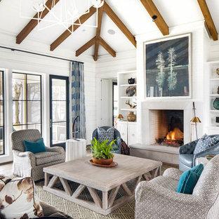 Imagen de sala de estar campestre con paredes blancas, suelo de madera oscura, chimenea tradicional y pared multimedia