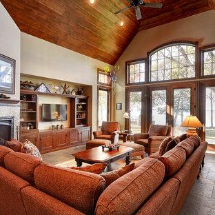 他の地域の大きいトラディショナルスタイルのおしゃれなファミリールーム (ベージュの壁、セラミックタイルの床、標準型暖炉、タイルの暖炉まわり、壁掛け型テレビ) の写真