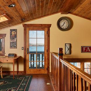 Modelo de sala de estar tipo loft, rural, pequeña, con paredes beige, suelo de madera oscura, chimenea tradicional, marco de chimenea de piedra, pared multimedia y suelo marrón
