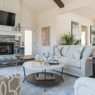 Mid-sized coastal open concept medium tone wood floor and brown floor family room photo with white walls, a standard fireplace, a stone fireplace and a wall-mounted tv