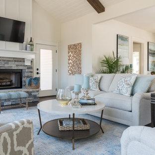 中サイズのビーチスタイルのおしゃれなファミリールーム (白い壁、無垢フローリング、標準型暖炉、石材の暖炉まわり、壁掛け型テレビ、茶色い床) の写真